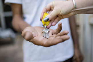 House keys being placed into an outstretched hand